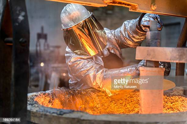 Worker cleaning molten metal flask in foundry, front view