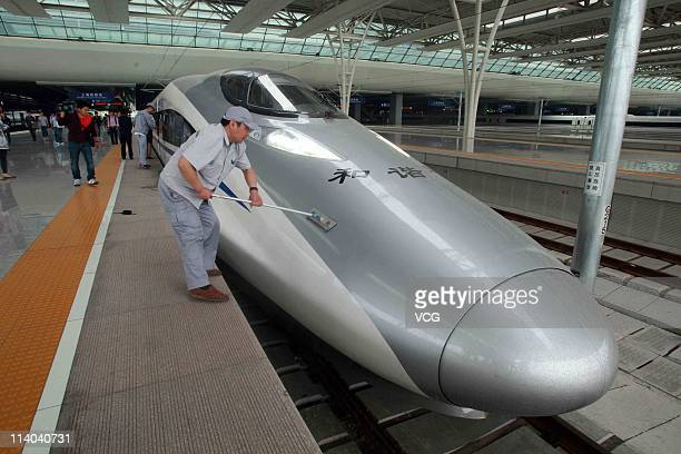 A worker cleans a CRH highspeed train at Shanghai Hongqiao Railway Station during its test run on May 11 2011 in Shanghai China After 3 years...