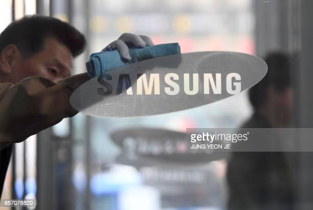 A worker cleans a glass door showing the logo of Samsung Electronics at a company's building in Seoul on March 24 2017 The world's biggest smartphone...