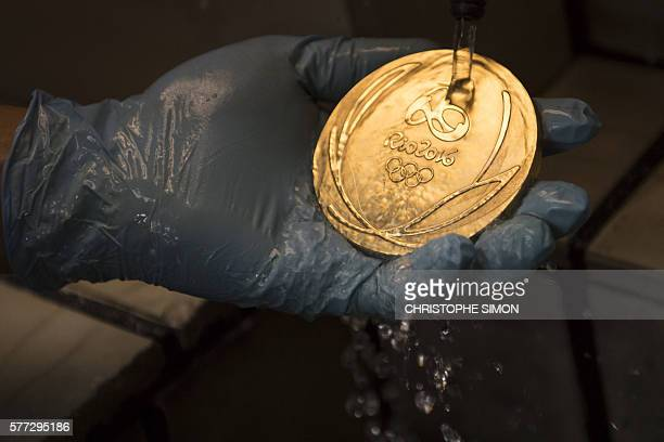 A worker cleans a gold medal for the Rio Olympic Games after its gold bath at a coin factory in Rio de Janeiro Brazil on July 18 2016 / AFP /...