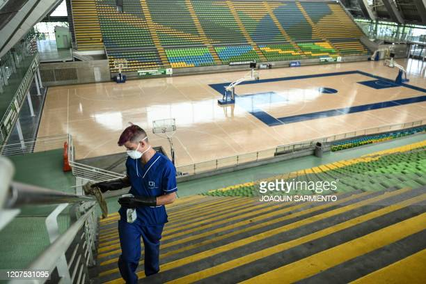 Worker cleans a handrail at the Ivan de Bedout basketball stadium in Medellin on March 17, 2020 after the closure of all sporting venues in Colombia...