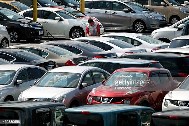 A worker cleans a Nissan Motor Co second hand vehicle displayed at a dealership in Yokohama Kanagawa Prefecture Japan on Monday July 28 2014 Nissan...