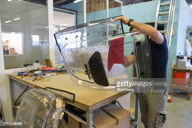 A worker cleans a plexiglass divider to be installed inside cars at Plexismart Srl in Guidonia close to Rome Italy on Wednesday May 20 2020...