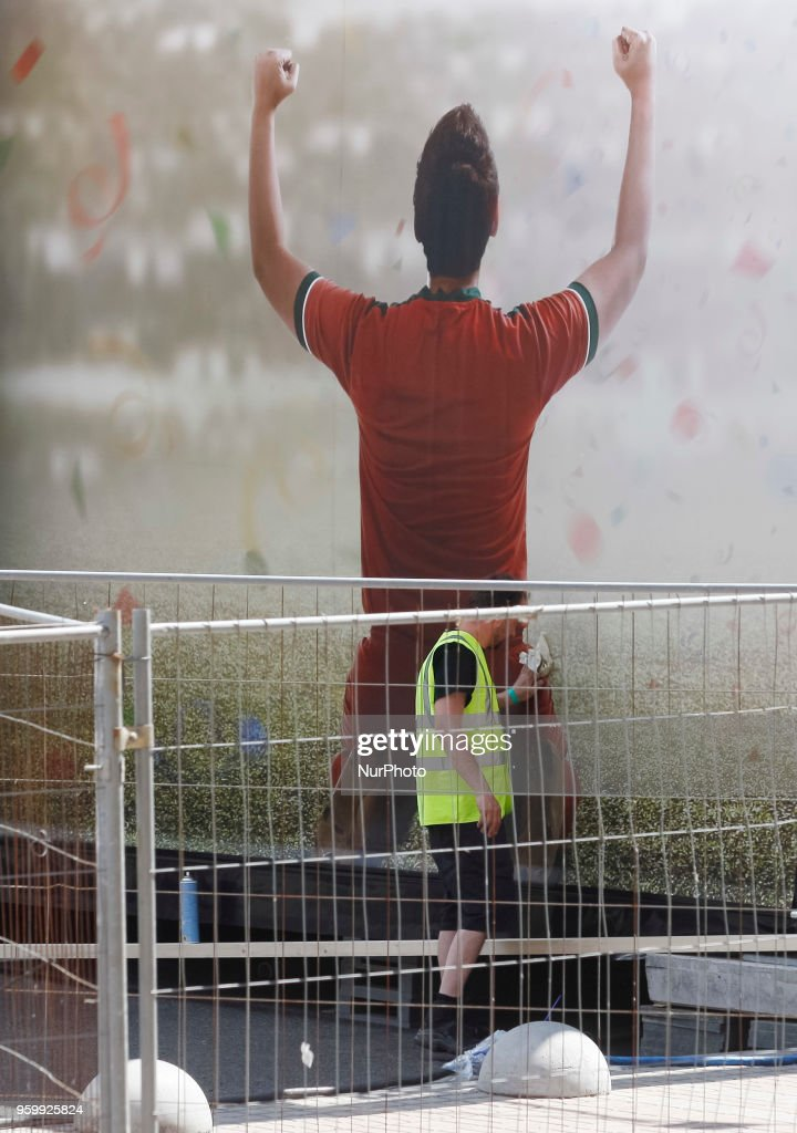 A worker cleans a poster in a fan zone of the UEFA Champions League final in central Kiev, Ukraine, 18 May, 2018. The football UEFA Champions League final match between Real Madrid and Liverpool FC next May 26 at the NSC Olimpiyskiy Stadium.
