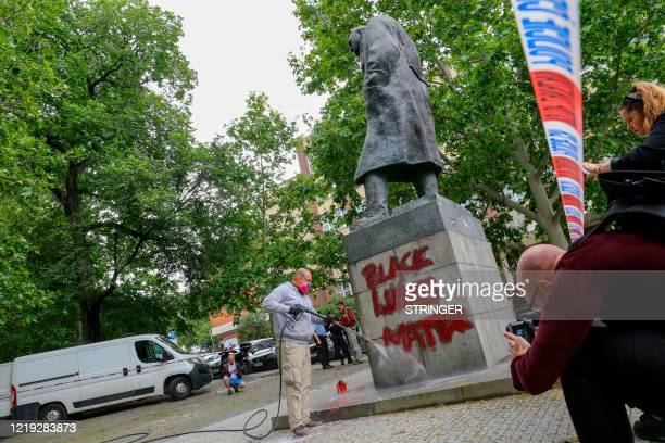 Worker cleans a statue of former British Prime Minister Winston Churchill which was spray-painted with the slogans 'Black Lives Matter' and 'He was a...