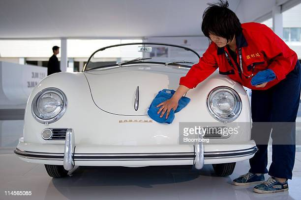 A worker cleans a vintage Porsche SE automobile on display at an event in Beijing China on Saturday May 21 2011 Porsche forecasts record 2011...