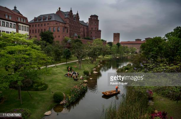 A worker cleans a waterway as office buildings are seen at Huawei's new sprawling 'Ox Horn' Research and Development campus on April 12 2019 in...