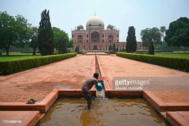 A worker cleans an artifical water channel at the 16th century Mughal monument Humayun's Tomb after it was reopened for visitors which was closed...