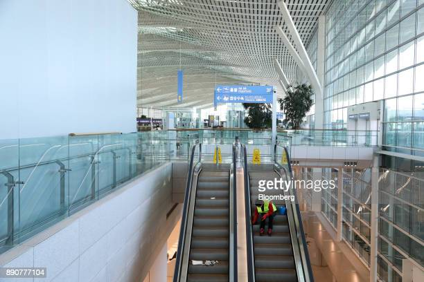 A worker cleans an escalator inside the nearly completed terminal 2 building during a media preview at Incheon International Airport in Incheon South...