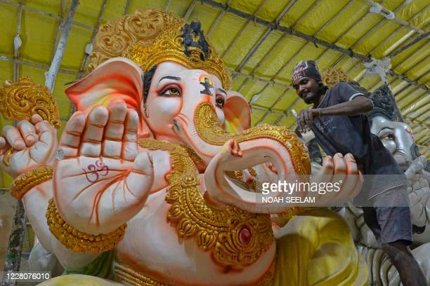 A worker cleans an idol of elephant headed Hindu god Ganesha at a workshop ahead of the Ganesh Chaturthi festival on the outskirts of Hyderabad on...