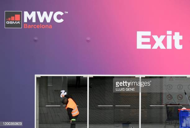 A worker cleans glass doors at the Mobile World Congress MWC venue on February 12 2020 at the Fira Barcelona Montjuic centre in Barcelona Organisers...