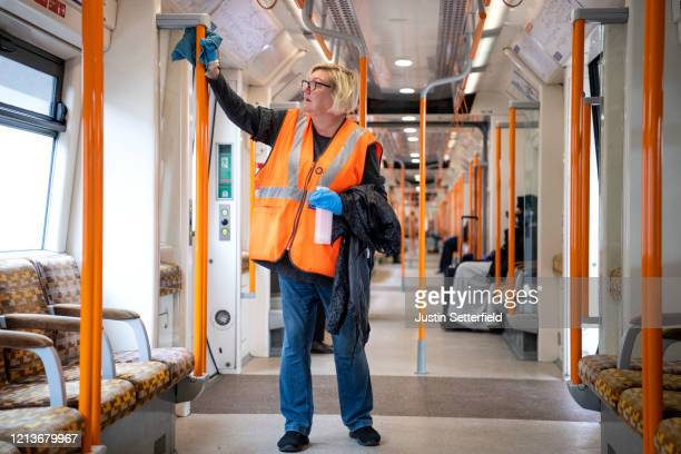 Worker cleans hand rails on a London Overground train at Stratford station on March 20, 2020 in London, England. Coronavirus has spread to at least...