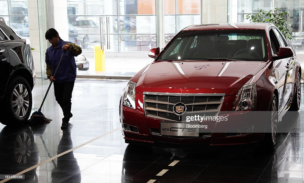 A worker cleans near a General Motors Co. Cadillac CTS vehicle displayed at a dealership in Shanghai, China, on Friday, Feb. 8, 2013. China's services industries grew at the fastest pace since August as gains in retailing and construction aid government efforts to drive a recovery in the world's second-biggest economy. Photographer: Tomohiro Ohsumi/Bloomberg via Getty Images