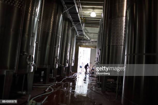A worker cleans near fermentation tanks at the Bodega Santa Julia production facility in Mendoza Argentina on Tuesday March 23 2017 The Argentine...