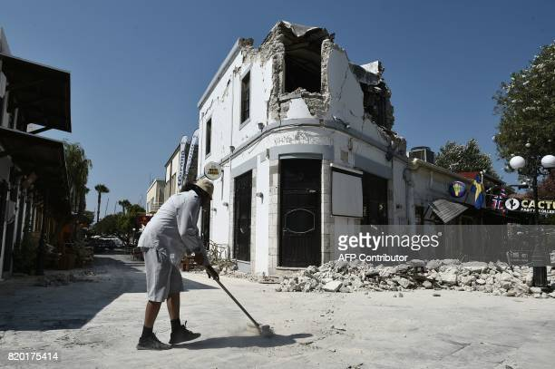 TOPSHOT A worker cleans outside a bar where two tourists were killed following a 65 magnitude earthquake which struck the region on July 21 2017 Two...