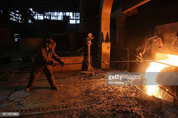 A worker cleans slag from an electric arc furnace in the steel making shop at the OAO Izhstal steel plant operated by OAO Mechel in Izhevsk Russia on...