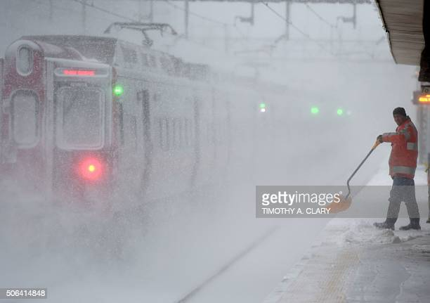 A worker cleans snow off the platform at the Metro North Train station in Greenwich Connecticut on January 23 2016 A deadly blizzard with...