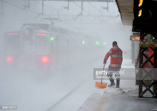 A worker cleans snow off the platform at the Metro North Train station in GreenwichConnecticut January 23 2016 A deadly blizzard with bonechilling...