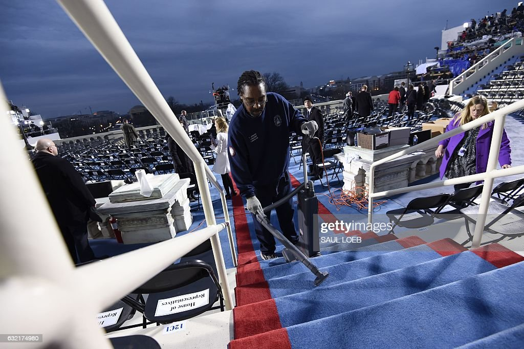 TOPSHOT - A worker cleans steps on the inaugural stand on January 20, 2017, at the US Capitol in Washington, DC, before the inauguration of US President-elect Donald Trump. / AFP / POOL / SAUL