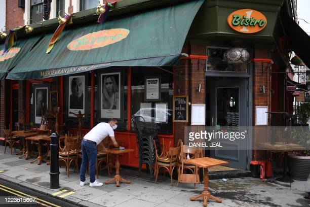 Worker cleans tables and chairs outside a restaurant in advance of the planned July 4 re-opening of restaurants in London on June 30 as coronavirus...