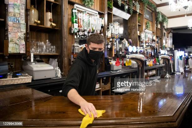 Worker cleans the bar in the Borough pub on December 4, 2020 in Cardiff, Wales. Following a firebreak period that ran from October 23 to November 9...