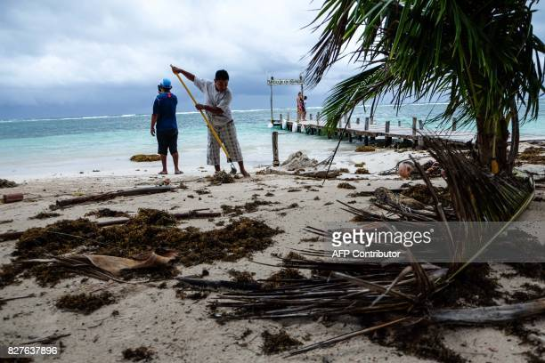 A worker cleans the beach in Mahahual Quintana Roo State on August 8 2017 after tropical storm Franklin made landfall on Mexico's Yucatan peninsula...