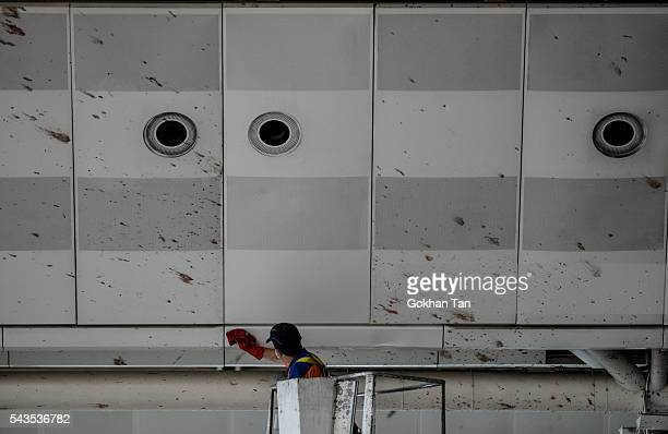 A worker cleans the blood splashed on the roof of the international departure terminal at the country's largest airport Istanbul Ataturk following...