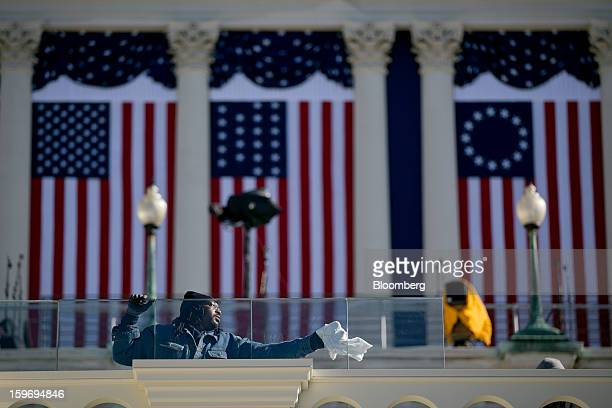 A worker cleans the bulletproof glass that surrounds the inaugural platform outside the US Capitol prior to the second inauguration of US President...
