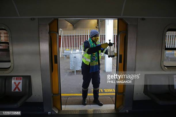 Worker cleans the doors of a train using disinfectant spray at Pretoria Station as the Passenger Rail Agency of South Africa resumes its operations...
