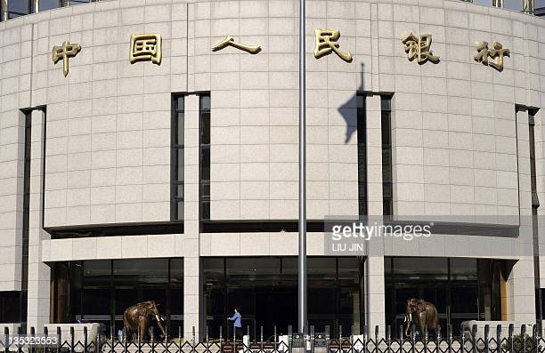 A worker cleans the entrance of the headquarters of the People's Bank of China in Beijing on December 9 2011 China's decadelong membership of the WTO...