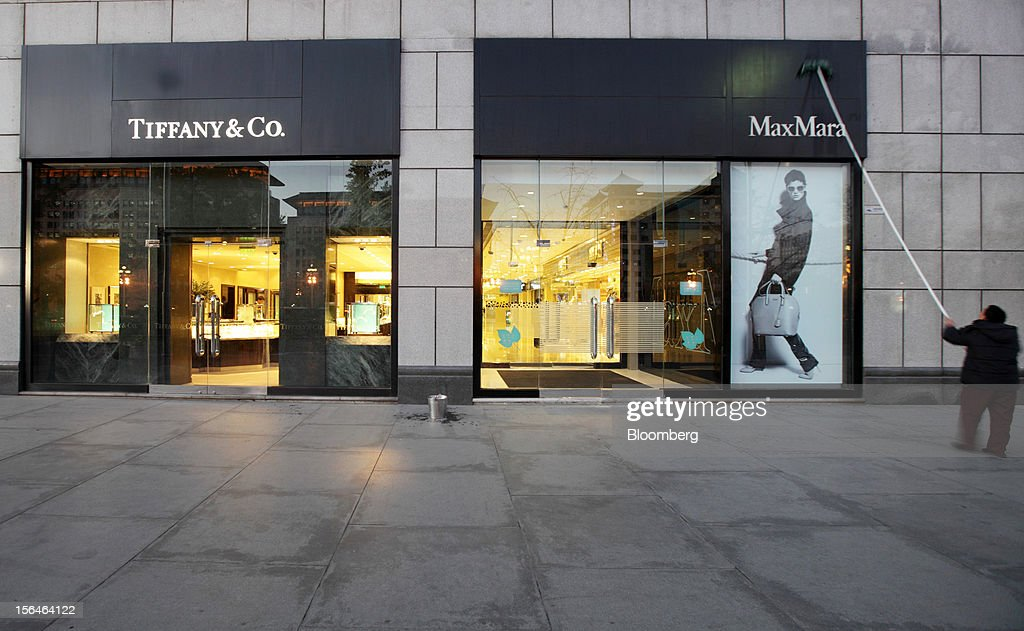 A worker cleans the exteriors of a building housing MaxMara and Tiffany & Co. stores in Beijing, China, on Monday, Nov. 12, 2012. China's retail sales exceeded forecasts and inflation unexpectedly cooled to the slowest pace in 33 months, signaling the government is boosting growth without driving a rebound in prices. Photographer: Tomohiro Ohsumi/Bloomberg via Getty Images