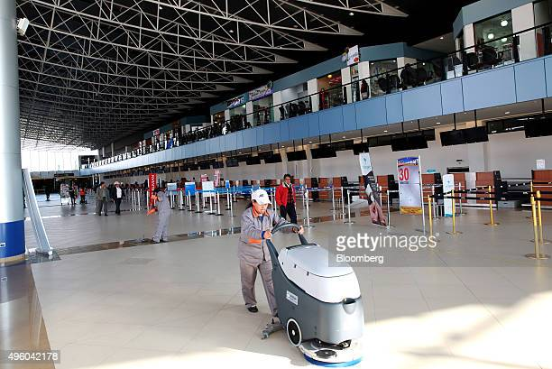Worker cleans the floor at the El Alto International Airport, which completed construction earlier this year, in El Alto, Bolivia, on Tuesday, Oct....