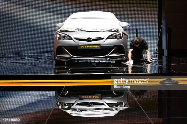 A worker cleans the floor beneath an Opel Astra Extreme automobile produced by General Motors Co on the company's stand ahead of the opening day of...