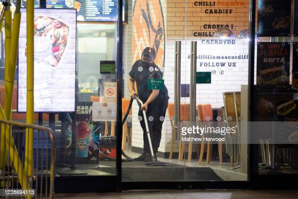 Worker cleans the floor in a closes restaurant on St. Mary Street on September 24, 2020 in Cardiff, Wales. Pubs, cafes and restaurants in Wales will...