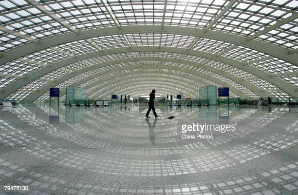 A worker cleans the floor in the Ground Transportation Center connecting the Beijing airport light rail line in the new terminal building T3 at the...
