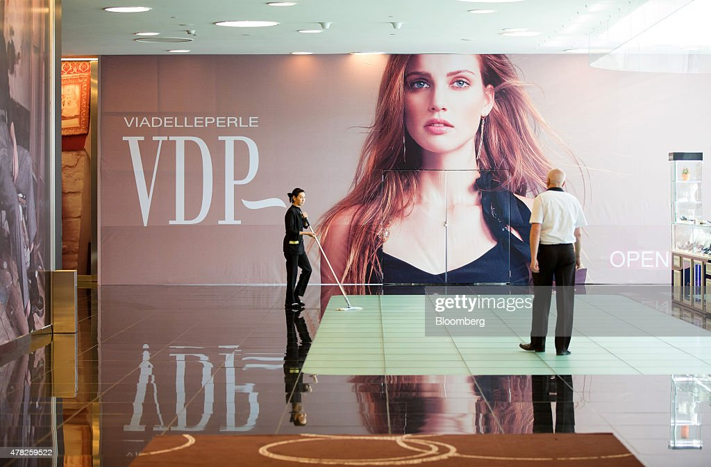 A worker cleans the floor near a Via Delle Perle (VDP) fashion advertisement at the Esentai luxury shopping mall in Almaty, Kazakhstan, on Tuesday, June 23, 2015. Kazakhstan completed its negotiations to become the 162nd member of the World Trade Organization, after 19 years of negotiations, and hopes to fully ratify its accession by Oct. 31. Photographer: Andrey Rudakov/Bloomberg via Getty Images