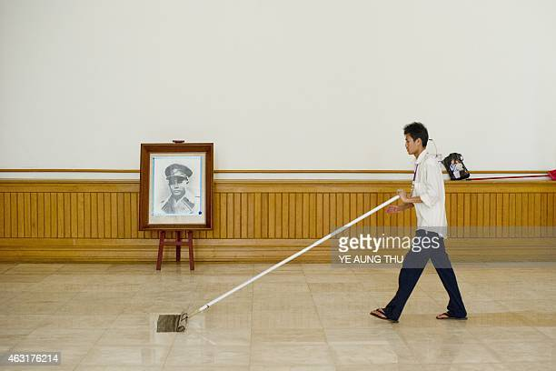 A worker cleans the floor next to a portrait of General Aung San inside the parliment in NayPyiDaw on February 11 2015 Celebrations will mark a...