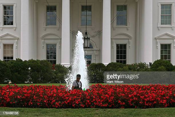 A worker cleans the fountain on the north lawn of the White House August 13 2013 in Washington DC President Obama and his family are currently...