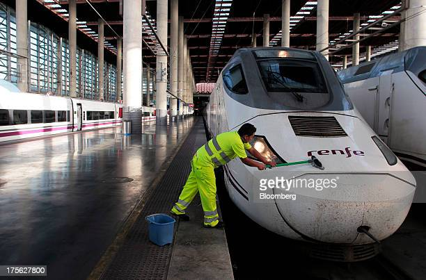 A worker cleans the front of an Alta Velocidad Espanola highspeed train operated by Renfe Operadora SC as it sits at a platform at Atocha train...