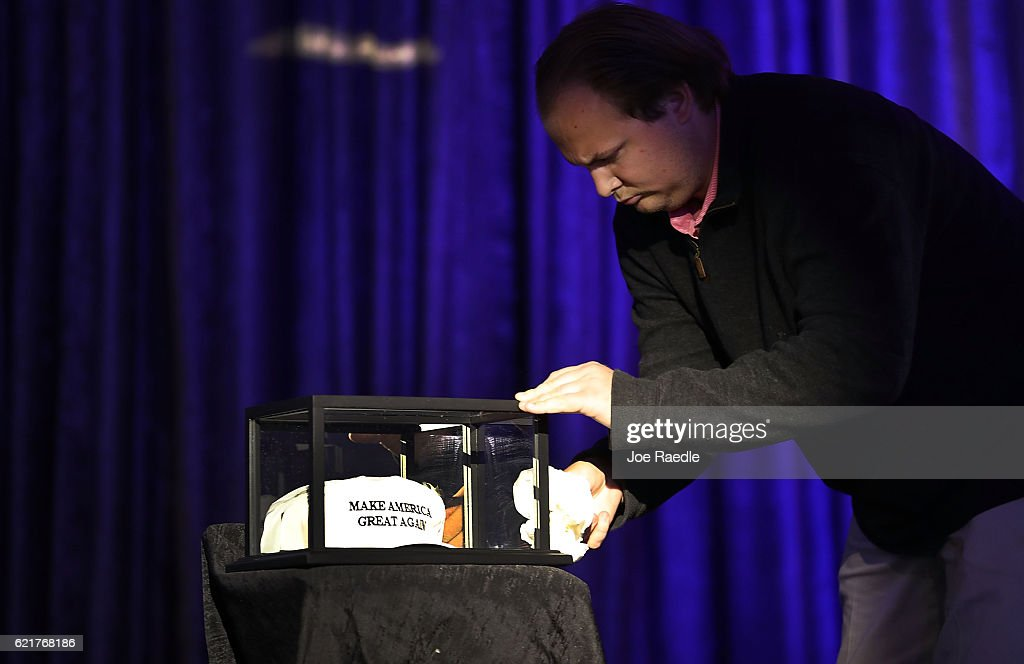 A worker cleans the glass case around the 'Make America Great Again ' hats on display, as the room for Republican presidential candidate Donald Trump election night party is prepared at the New York Hilton Midtown on November 8, 2016 in New York City. Voters head to the polls to decide the next President of the United States.
