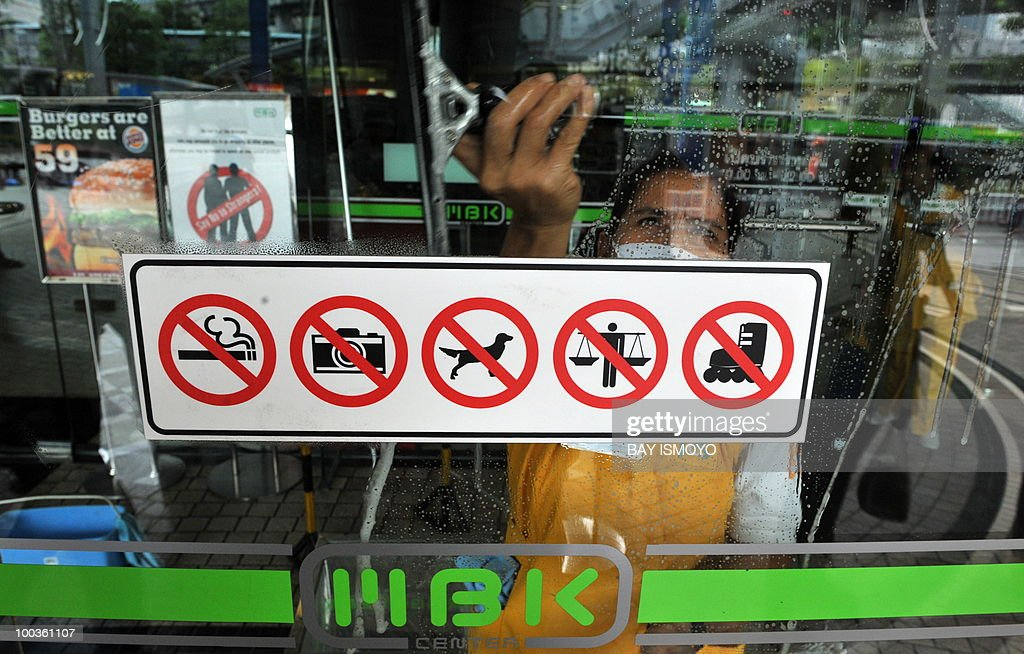 A worker cleans the glass door of a shopping mall in downtown Bangkok on May 24, 2010. Thailand's prime minister said that Bangkok would get back to business on after a massive clean-up, and defended a crackdown on protest rallies that unleashed a rampage of arson and looting. AFP PHOTO / Bay ISMOYO