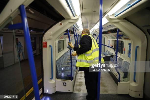 Worker cleans the hand rails inside a London Underground train car in London on March 25 after Britain's government ordered a lockdown to slow the...