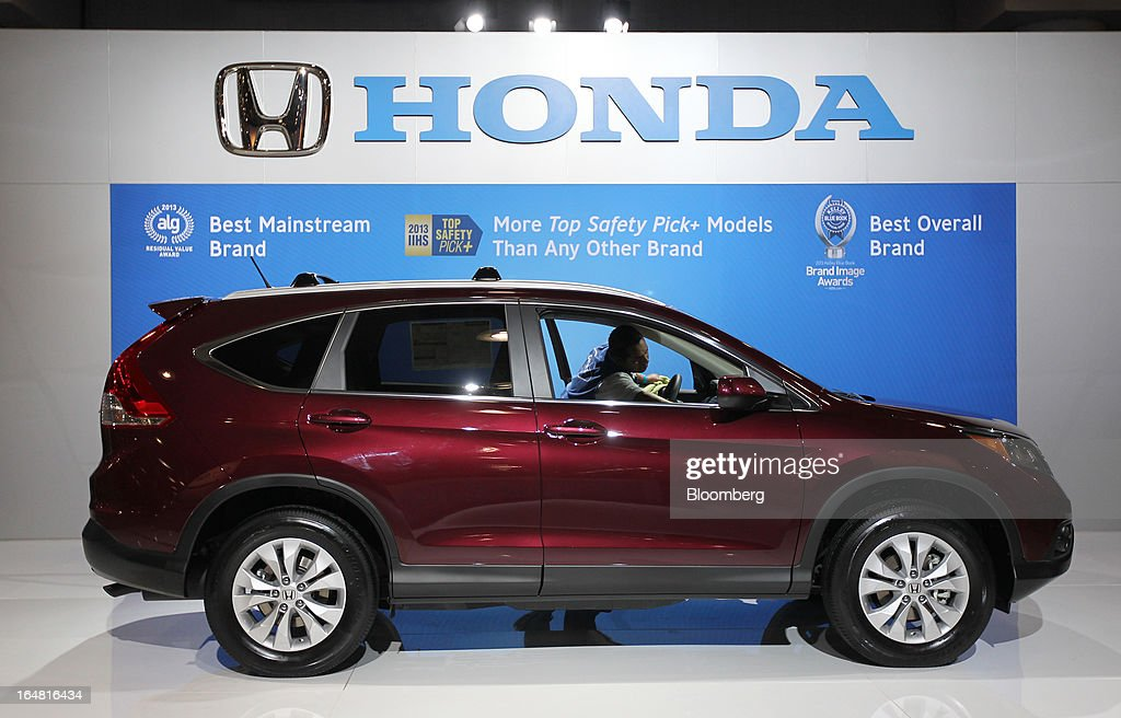 A worker cleans the interior of a Honda Motor Co. CR-V vehicle displayed at the company's booth during the 2013 New York International Auto Show in New York, U.S., on Thursday, March 28, 2013. The 113th New York International Auto Show, which runs from March 29 to April 7, features 1,000 vehicles as well the latest in tech, safety and innovation. Photographer: Jin Lee/Bloomberg via Getty Images