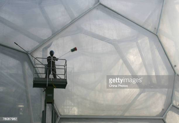 A worker cleans the membrane in the structure of the National Aquatics Center dubbed the Water Cube on November 25 2007 in Beijing China The National...