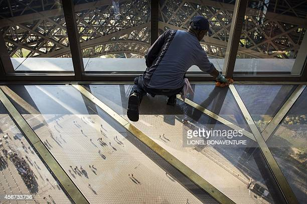 Worker cleans the new glass floor at the Eiffel Tower in Paris on October 3, 2014. The Eiffel Tower is inaugurating a new glass floor on October 6...