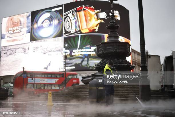 Worker cleans the pavement in Piccadilly Circus in central London on December 18, 2020. - The British capital was placed in the toughest Tier 3 of...