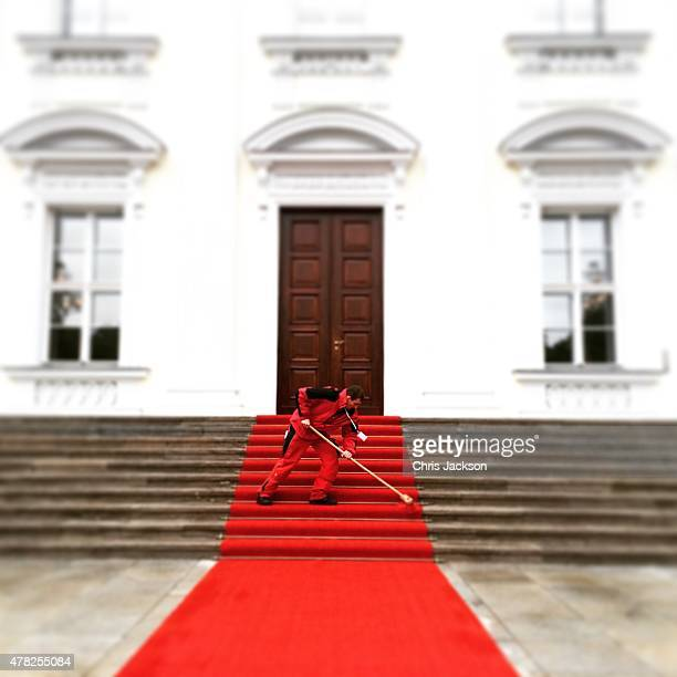 A worker cleans the red carpet ahead of the Queen's arrival at the Schloss Bellevue Palace on the second day of a four day State Visit on June 24...