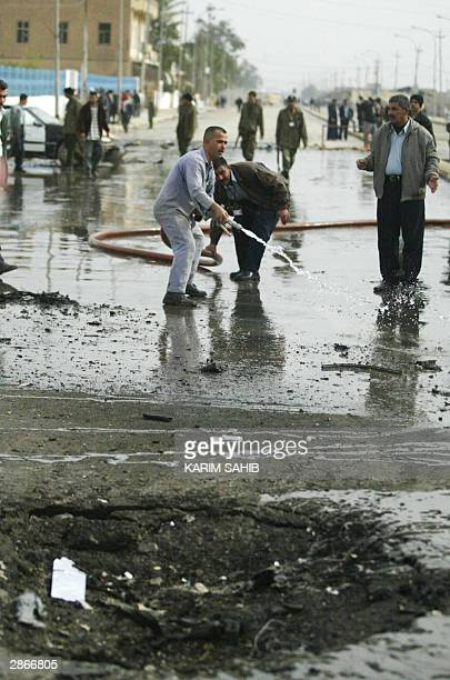 A worker cleans the scene where a suicide car bomber blew himself up outside a police station in Baquba 50km northeast of Baghdad 14 January 2004...
