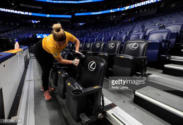 Worker cleans the seats after the announcement of the cancellation of the SEC Basketball Tournament at Bridgestone Arena on March 12, 2020 in...