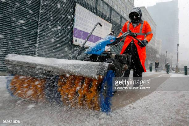 A worker cleans the sidewalk during a snow storm on March 21 2018 in Jersey City New Jersey At least 12 to 15 inches are expected in parts of...